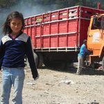 Girl living in poverty working at garbage dump